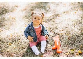 小女婴穿着雨靴坐在公园里_5852221