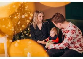 年轻的家庭带着女婴坐在圣诞树旁_6426685