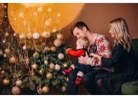 年轻的家庭带着女婴坐在圣诞树旁_6426688