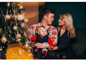 年轻的家庭带着女婴坐在圣诞树旁_6426689
