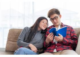 年轻的美女和帅哥坐在沙发上看书_5392724