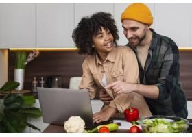年轻夫妇在厨房里用笔记本电脑工作_6121113