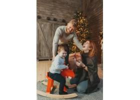 年轻的高加索家庭妈妈爸爸儿子在壁炉圣诞树_6136045