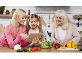女人们在厨房里看着平板电脑_6315360