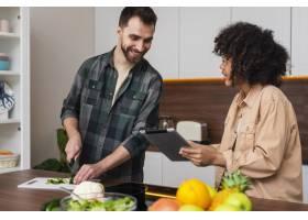 女人向男人展示平板上的东西做饭_6121063