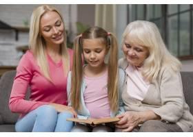 女儿和家人坐在沙发上看书_6317992