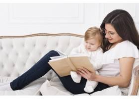 妇女抱着婴儿坐在沙发上看书_6071167