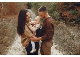 可爱时髦的一家人在秋天的田野里玩耍_6239300