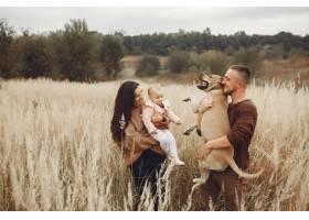 可爱时髦的一家人在秋天的田野里玩耍_6239303