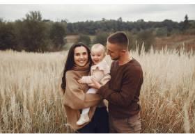 可爱时髦的一家人在秋天的田野里玩耍_6239305