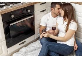 可爱的情侣在厨房地板上喝酒_6363768