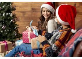 圣诞树附近拿着礼物的中景快乐的孩子们_5750060