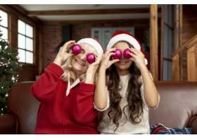 中等镜头的奶奶和孩子拿着圣诞球摆姿势_5750110