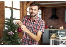 中枪男子用粉红色的球装饰圣诞树_5751172