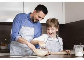 低角度微笑的父子俩在做面团_6157563
