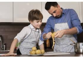 低角度的儿子和爸爸在清洗土豆_6157569