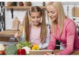 全家人在厨房做饭看着平板电脑_6319425