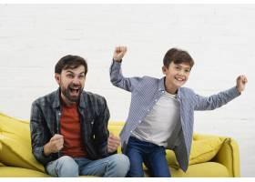 兴奋的儿子和父亲坐在沙发上_6037397