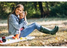 一位年轻的母亲带着她的小女儿在秋季公园野_5852231