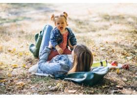 一位年轻的母亲带着她的小女儿在秋季公园野_5852233