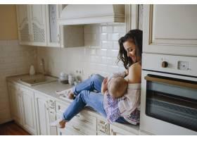 一位微笑的母亲在厨房里抱着婴儿_5697752
