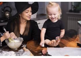 一位母亲和她的孩子们做万圣节饼干的前景_5481616