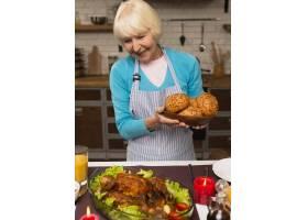 一位老妇人拿着一个装有面包的盘子看向别_5682543