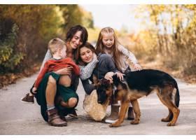 秋天公园里的母亲带着孩子和狗_5852277