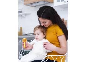 母亲抱着婴儿玩玩具_6071137