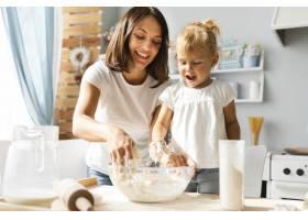 漂亮的妈妈和漂亮的女孩在准备面团_5918588