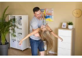 父亲侧着身子和女儿在房子里玩耍_6342812