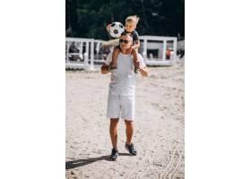 父子俩在海滩上踢足球_5507441