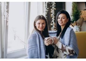 母亲和女儿在靠窗的厨房一起喝茶_6426785