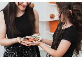 母亲和女儿拿着一个装有饼干的盘子_5481442