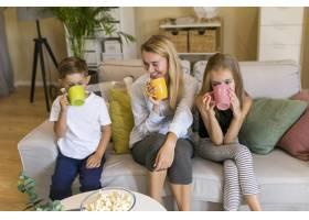 母亲和她的孩子们坐在杯子前喝酒_6321733