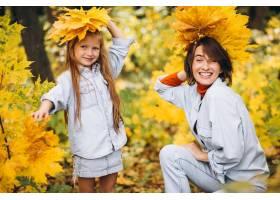 母亲和她的小女儿在满是金叶的森林里_5852329