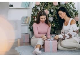 母亲和成年女儿在圣诞树旁送圣诞礼物_6426757