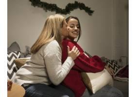 母亲在圣诞节亲吻她的女儿_5986362