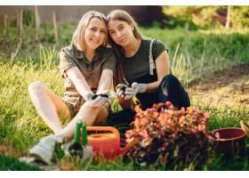 母亲带着一个女儿在房子附近的花园里工作_5251365