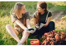 母亲带着一个女儿在房子附近的花园里工作_5251366