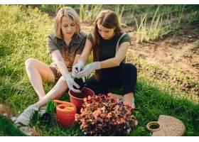 母亲带着一个女儿在房子附近的花园里工作_5251367
