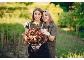 母亲带着一个女儿在房子附近的花园里工作_5251374