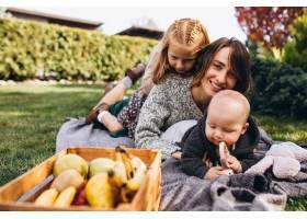 母亲带着两个孩子在后院野餐_5852306