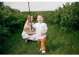 母亲带着儿子在夏日的田野里玩耍_5252257