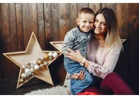 母亲带着可爱的儿子庆祝圣诞节_5557893