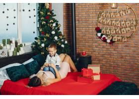 母亲带着可爱的儿子庆祝圣诞节_5557898