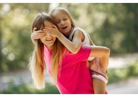 母亲带着女儿在夏季公园玩耍_5911561