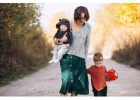 年轻的母亲带着两个儿子在公园散步_5852282