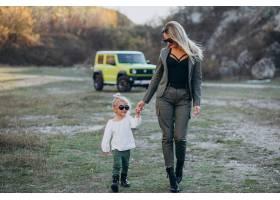 年轻的母亲带着可爱的小女儿开车在公园里_6213762