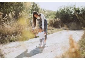 年轻的母亲带着她的孩子在田野里散步_5852262
